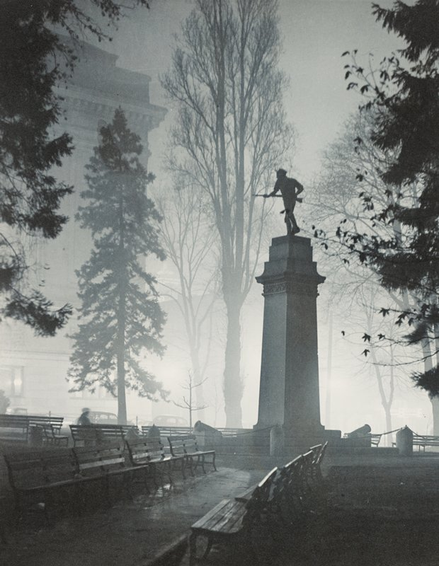 soldiers' monument, Portland, Oregon; benches in park in city around monument with sculpture of soldier with gun on top