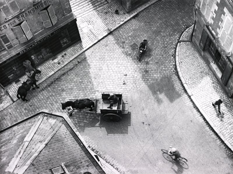 aerial view of a street with horse-drawn cart at center, turning corner; figure on bicycle behind cart; figure on motorbike, URQ; another horse at left center