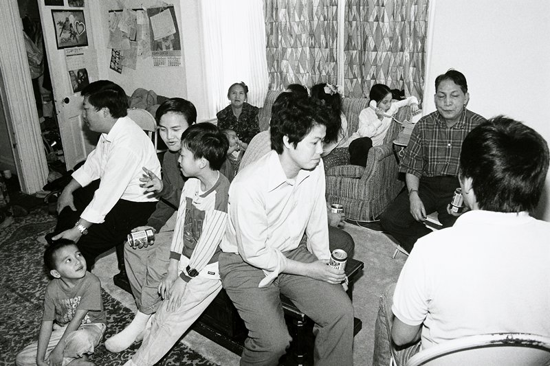 black and white photo of group of people in living room; several are holding 'Mountain Dew' cans