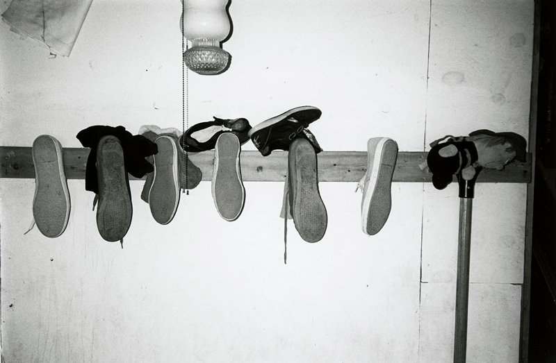 black and white photo of eight shoes on wall peg board