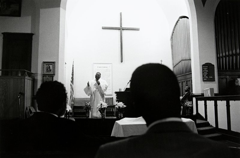 black and white photo of preacher with microphone addressing congregation
