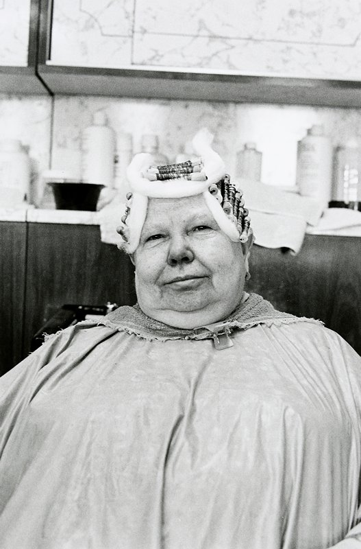 black and white photo of woman with rollers and cotton strips in hair