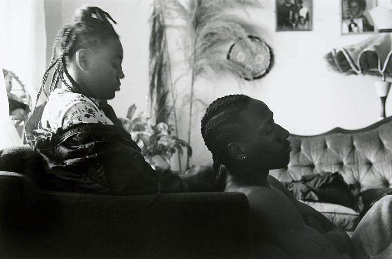 black and white photo of woman in chair, man sitting in front of her, both wearing braids