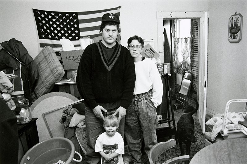 black and white photo of man, woman, child standing in front of American flag