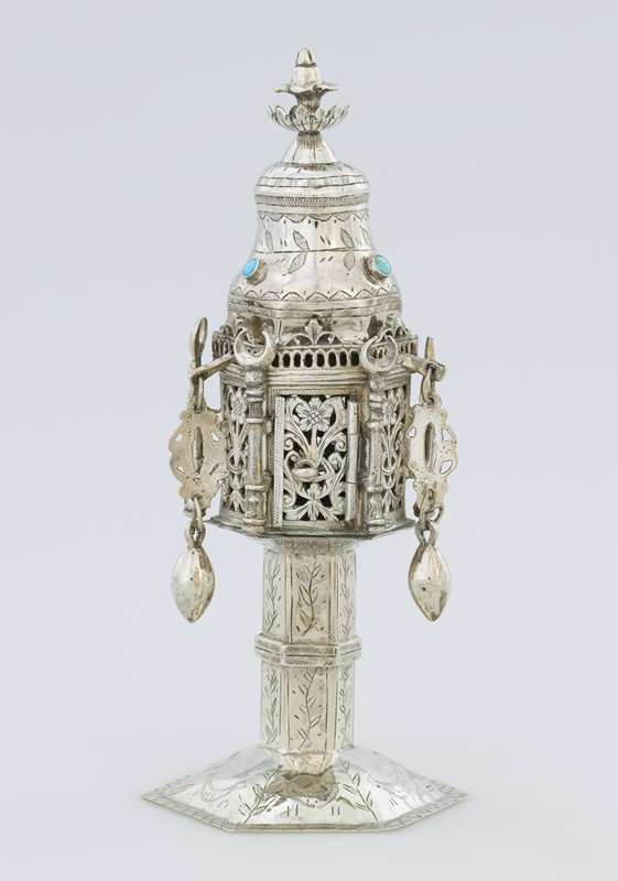 hexagonal shaped container on stem and base; top decorated with incised vines and 3 inset turquoise stones; openwork floral body with 3 hanging pendants on movable arms; crescent-topped bars at corners; incised decorations on stem and base