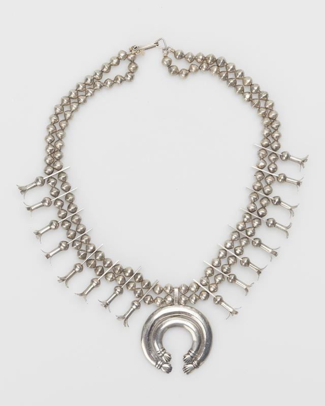 Double strand of slightly flattened silver beads; on either side of naja 8 4-pronged squash blossoms attached to beads with long, twice pierced rectangular extensions; naja is 2 cast bands both ending in two sets of hands; string with metal clasps. J.#414, Cat.#396.