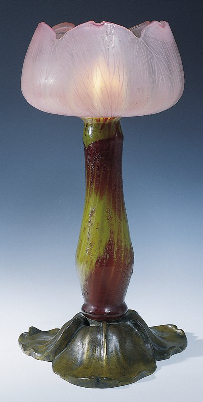 Cameo art glass formed as an open lotus-like blossom with a long throat set into a bronze socle of leafage