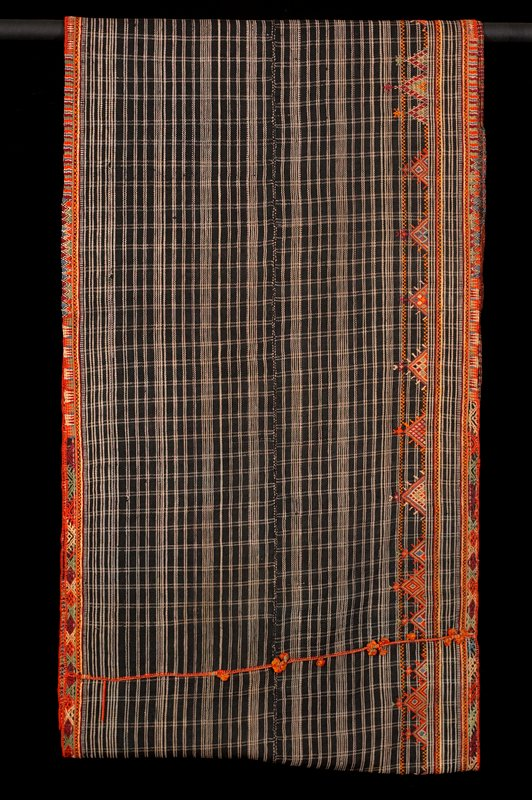 blue wool with grey checks; vertical seam decorated with 15 tassels; top and bottom embroidered with bands of various geometric designs; bottom edge has geometric designs above band; two panels stitched together lengthwise; woven fabric; woven border; orange, red, blue