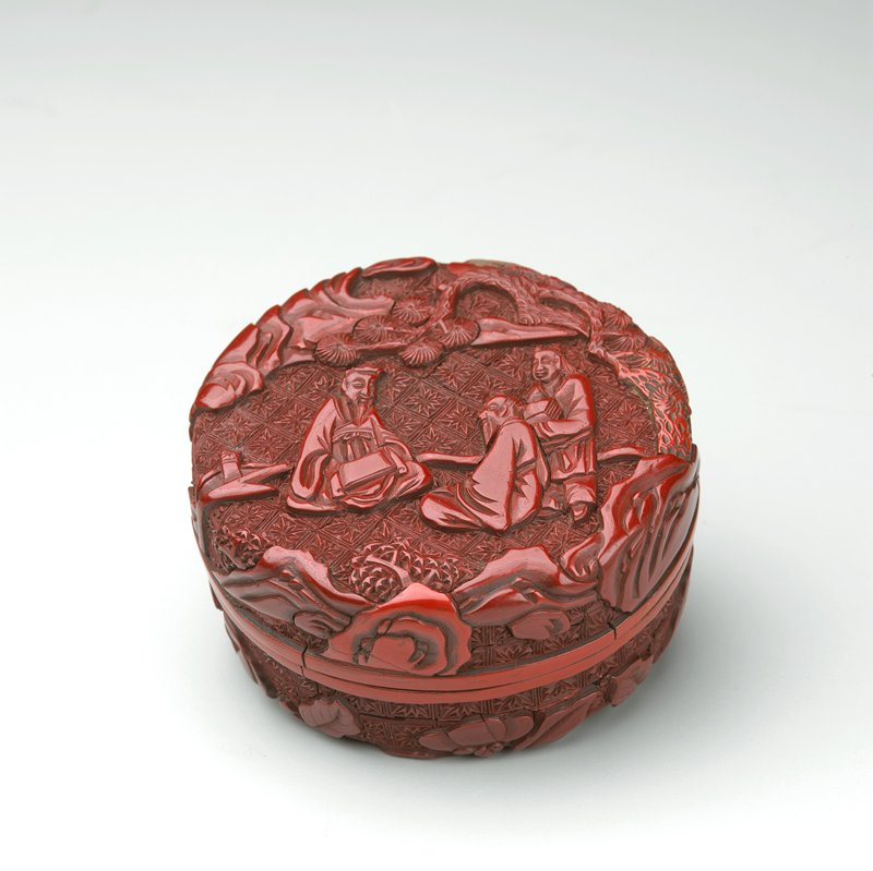 3 figures surrounded by foliage and rocks on cover; bottom has prunus flowers and branches; diaper ground overall; carved red lacquer