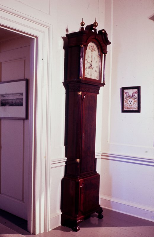 clock, long case; hood has scroll top and brass finial; painted domed dial framed by fluted columns with capitals and bases gilded; body framed by quarter round columns rests on feet in bracket form terminating in claw-and-ball and carved with acanthus; band of carved fretwork below dial