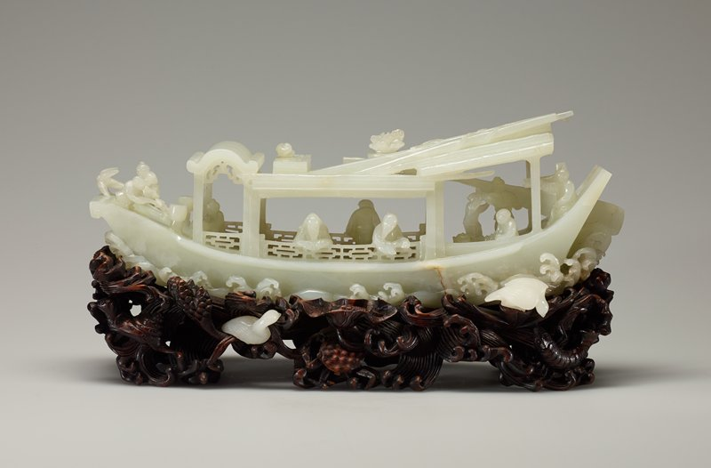 A long sampan with several figures on board, carved with elaborate details and with wave motifs around the base, fitted with teakwood stand with white jade birds inset in the wave carving.