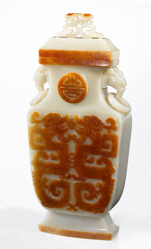 Carved from white and brown jadeite in vertical strata, the flattened shield-shaped vase carved with pairs of stylized dragons holding a pearl in theior mouths, below a shou medallion on the neck, the decoration on each side in bright reddish-brown colored stonein relief against a pure white background, the neck with masl and loose ring handles, and the rim with more of the reddish-brown skin of the stone used to highlight a fretwork band, the cover with double dragon-loop finial holding a pair of loose rings.