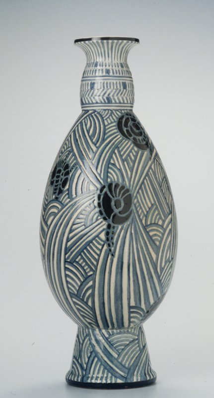 Oviform with slightly swollen neck with everted rim on tapering cylindrical foot, covered in a white glaze, over which a dark and pale blue segmented curving linear decoration, with small areas filled in dark blue.