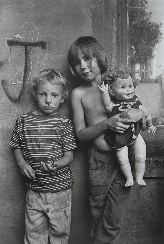 two dirty children: blonde child on left wearing striped shirt and light-colored pants; dark-haired child on right is bare-chested and holds a doll
