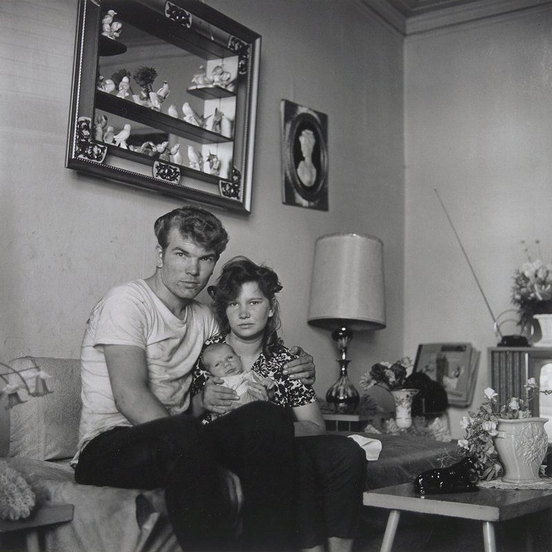 young man at left with his PL arm around a young woman holding a baby; couple are seated on a small couch in a living room