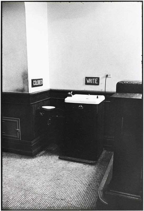 "large console drinking fountain with a sign reading ""white"" over it; small basin drinking fountain to left with a sign reading ""colored"""