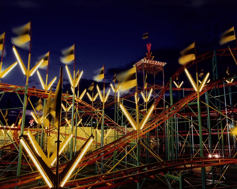 "red roller coaster track with yellow v-shaped lights and yellow and black flags; tower with red lights reading ""TORNADO"" in URQ"