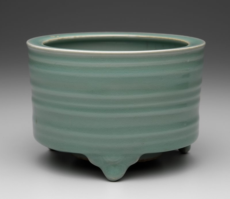 cylindrical form with 3 stylized trefoil clouds for feet; body decorated with 3 bands of 3 raised ridges; blue-green bubbly celedon glaze