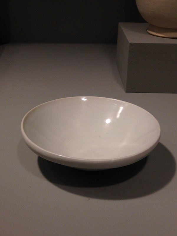 small bowl with white glaze with light blue tinge; unglazed foot