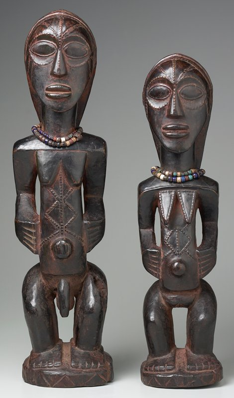 standing male figure with knees slightly bent; zigzag patterns on stomach; long hair; 2 strands of multicolored beads around neck