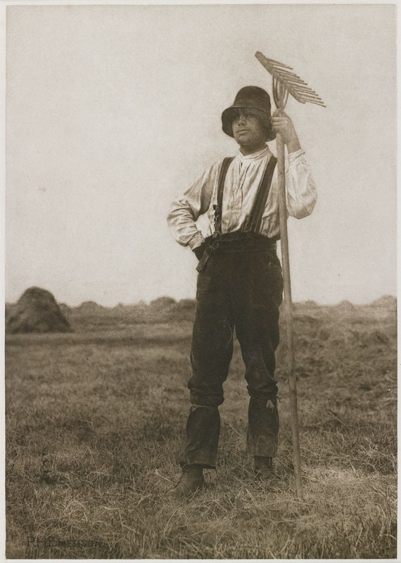 man standing in a field with haystacks in background; man wears a hat, long-sleeved shirt, pants with suspenders and boots, and holds a rake with his PL hand; sheet cut from book