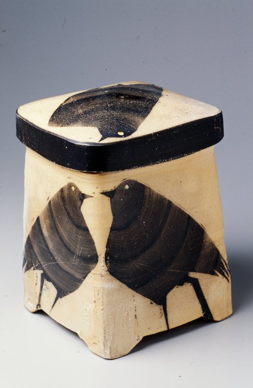 square shaped with rounded corners; feet at corners; slightly domed cover; brown interior; yellow exterior with black bird on each side of jar and on cover