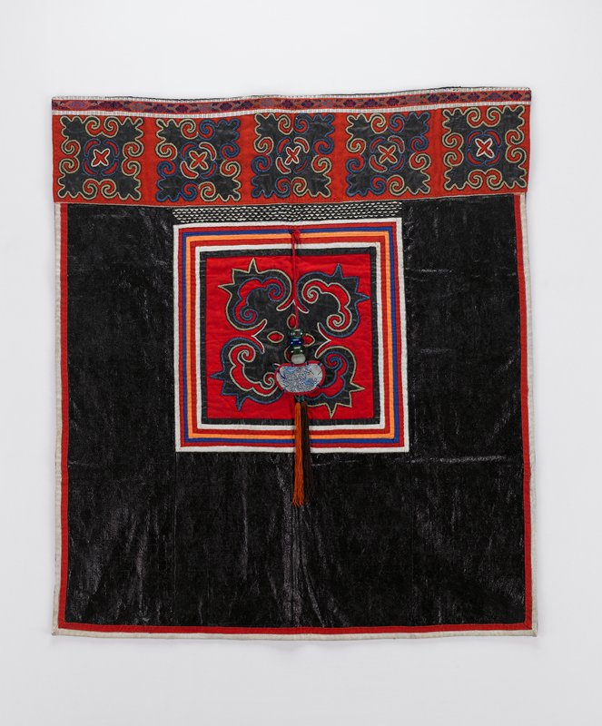 shiny dark blue fabric with red lower border with 5 organic appliques; large central organic applique on red; orange and brown tassel at center with bean-shaped fabric decoration and 4 beads