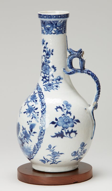 ewer; long cylindrical neck shows sprays of flowers; band of flowers forms border of neck and repeat motif (white circles within blue hexagons) reappears on slightly projecting lip; curved blue handle in shape of dragon, head turned backward, jaws wide open; (upper part of jaw broken)