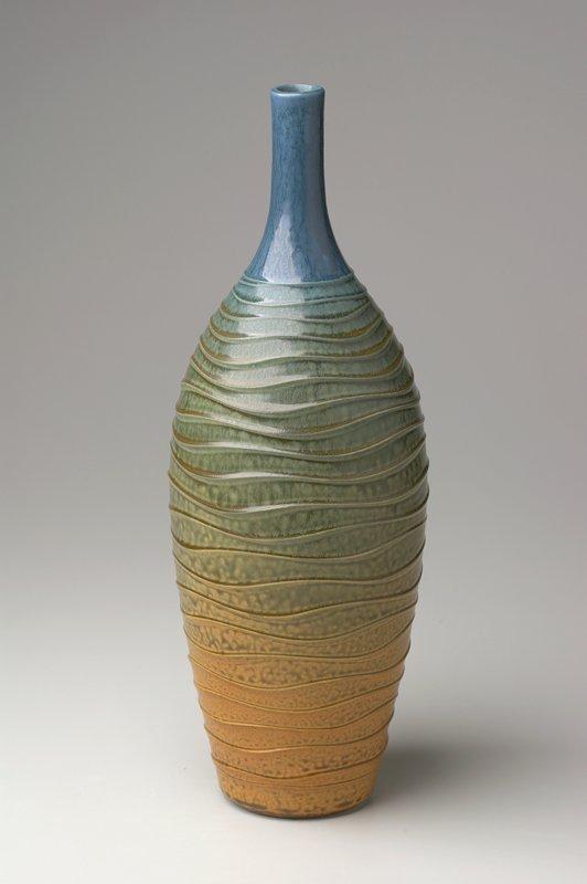 bottle with slightly flaring shoulder and long, narrow neck; shaded glaze, bottom to top: orange, green, blue; wavy horizontal ribs on body