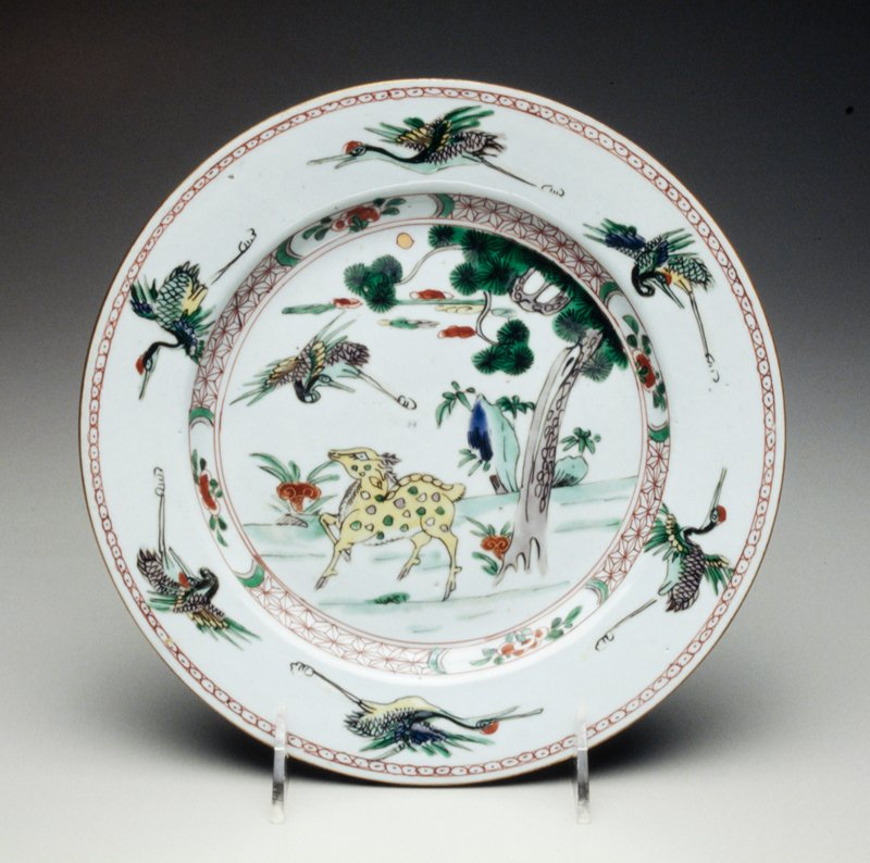 famille verte plate decorated with yellow spotted deer on grassy bank and crane in flight, floral patterned border with 6 cranes in flight