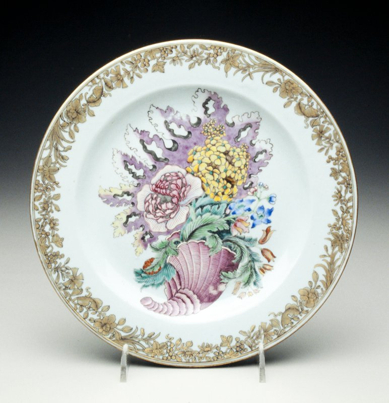 european design plate decorated with large famille rose pink cornucopia of elaborate foliage backed by exotic shaded puce leaf, border with black and gilt dense meander and grapes