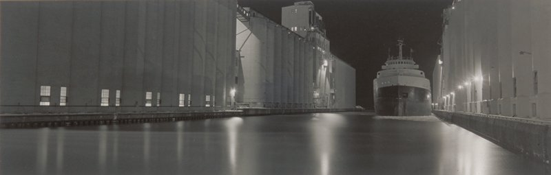 night time; large freighter moving in a narrow canal lined on both sides by grain elevators