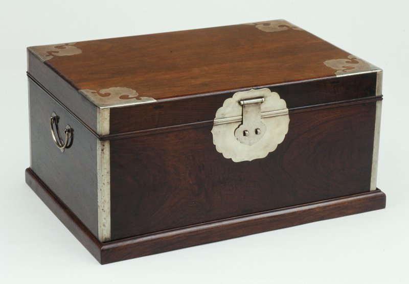large trunk with three panel top; inlaid foliate paktong lockplate; molded edged; cloud shaped upper corner plates, c-shaped handles; dark finish; molded stepped plinth; bottom comes off