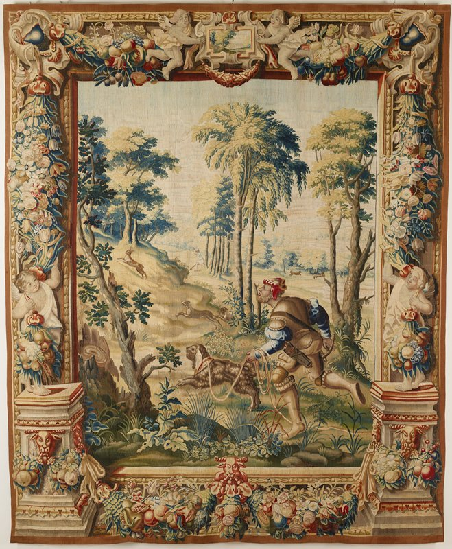 One of set of four tapestries, with landscape scenes and figures inspired from the Hunts of Maximilian, now in the Louvre and woven after the cartoons of Bernard Van Orley, also preserved in the Louvre. Woven at sides with bases sustaining figures of putti and decorated with rams' heads. Embellishment of festoons, pendant bunches of fruits and flowers. Top border with scrolled, oblong cartouche in center, which contains a miniature landscape scene, supported by winged cherubs. Similar cartouche, with swags of fruit and flowers in bottom border. Hunting the Hare In immediate foreground a bearded huntsman, wearing a crimson cap, a blue doublet with half armor and short trunks, holds a spaniel in leash. He runs towards left where two hounds pursue the hare up a hill. In middle distance another huntsman, with spear, holds off two other hares.; warp undyed wool, 8-8½ ends per cm., weft dyed wool and silk, 24-36 ends per cm.