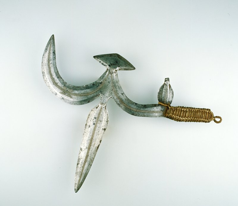 two-pointed blade, straight point at center, curved point at back, two protrusions at back of blade, handle wrapped with cloth and rope
