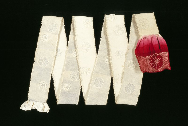 bolt of kimono length; tied, ready for dyeing, white; one end dyed red with ties removed, reveiling floral and diamond background pattern