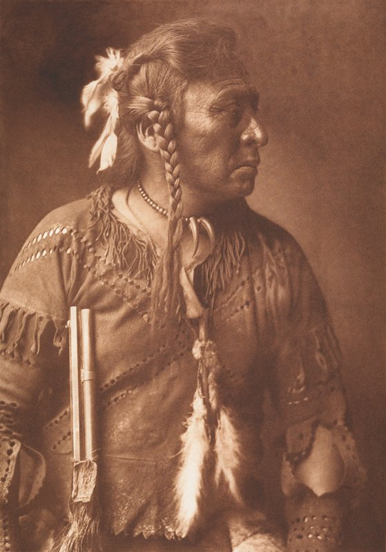 portrait of a Native American male dressed in traditional clothes holding a rifle at his side with the proper right hand; image is from waist up; man's face seen in profile as he is looking to his proper left side