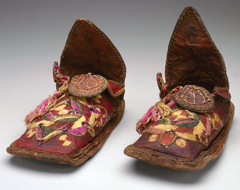 irregular rectangular smooth leather sole; leather upper dyed red with embroidery, circular designs; four flaps at opening, two small lobed ears and larger tongue which lays over embroidery, and a tall pointed heel panel. Surface ornamentation (Needlework)