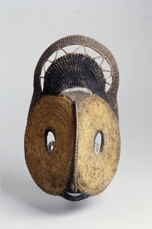 pointed face with flat yellow sides and large open white eyes; loop at nose, small mouth opening; short, rounded headdress of solid black, one zigzag row and outer dark band
