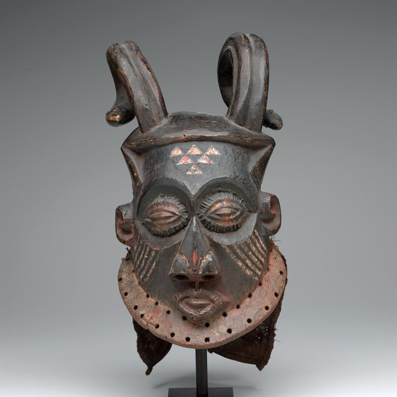 large copper eyes and copper lips; wide nose with large nostrils; 6 white triangles on forehead; white and black lines on cheeks; long curved horns; cloth on back