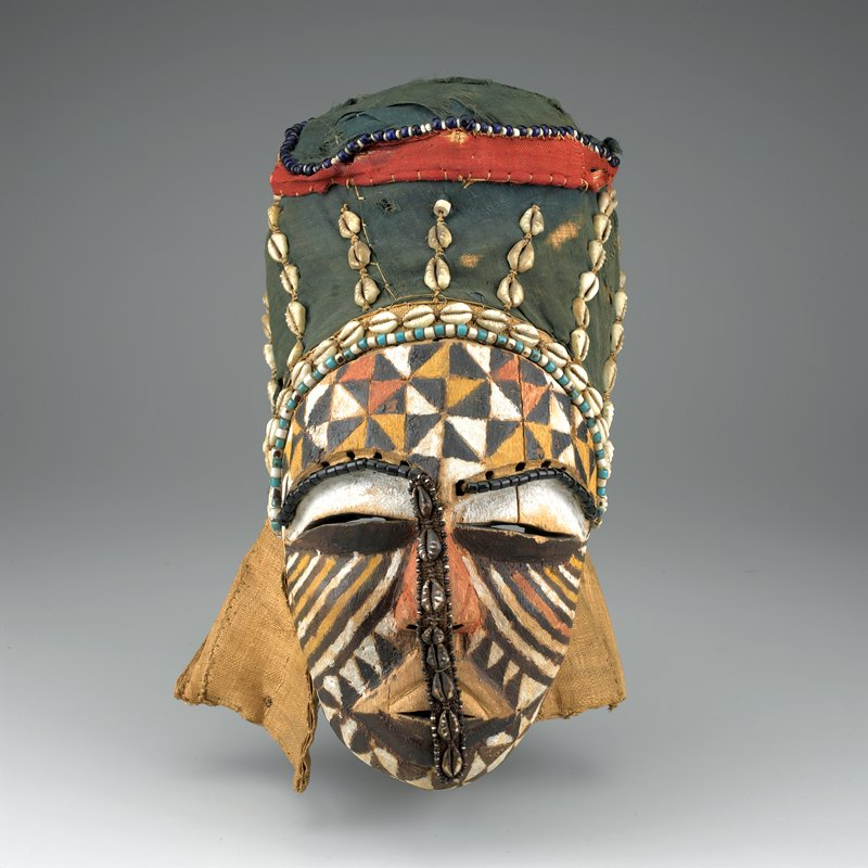 small face with wide slit eyes; face decorated with white, tan and brown lines and triangles; cloth band with shells down center of face; blue and red cloth at top of head decorated with shells and beads