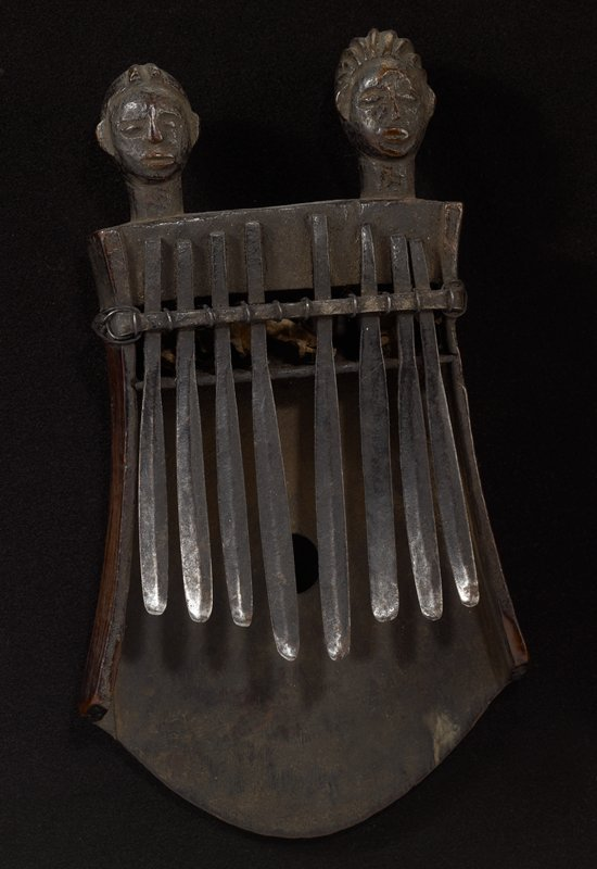 8 metal bars of varrying lengths attached to a 3-sided wood container with 2 carved heads at top; plant materials in space at top of bars