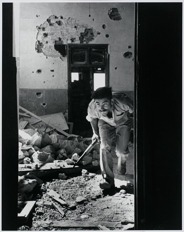 black and white photograph of man carrying a gun amidst the rubble of a building