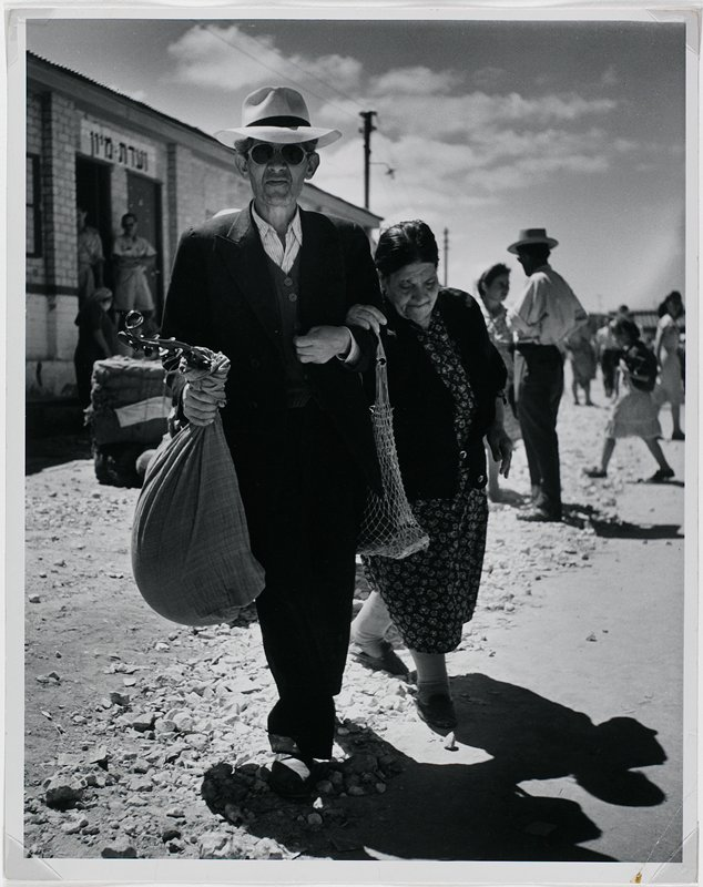 black and white photograph of man wearing hat and sunglasses carrying a bag; older woman in print dress holding his arm; May-June 1949