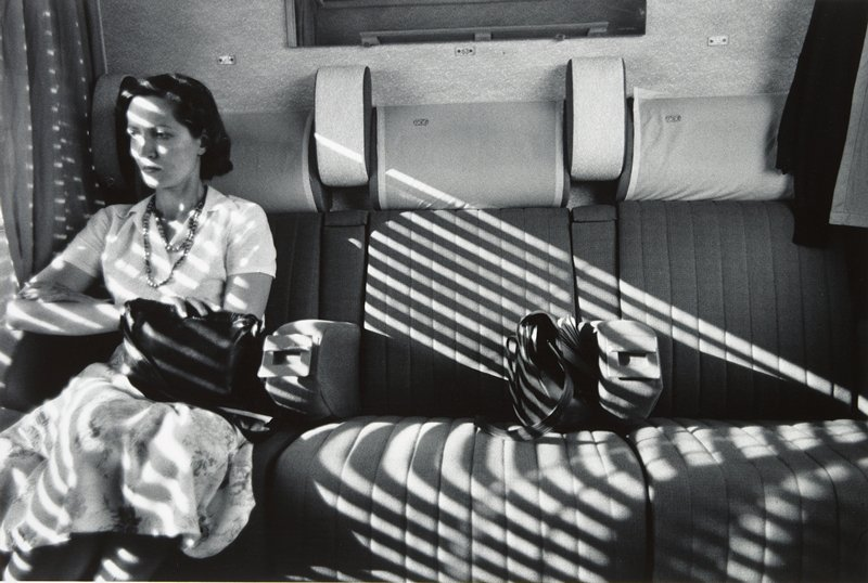 seated woman holding handbag, sitting next to window in a row of three seats