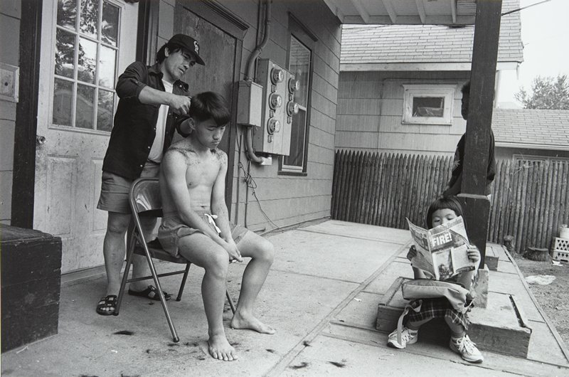 black and white photo of boy seated on porch getting a haircut; little girl seated, reading