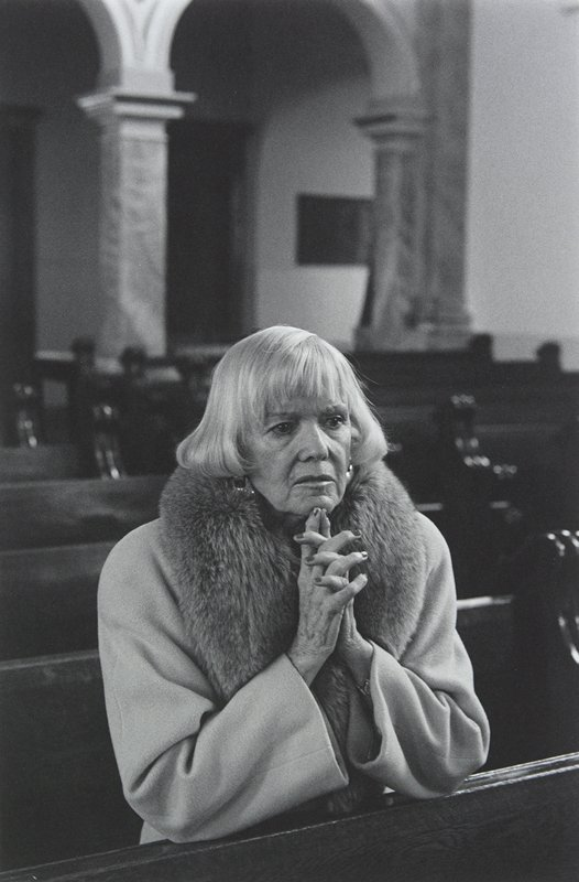 black and white photo of blonde woman praying in church pew