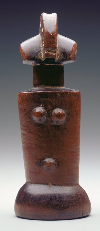 female figure; no face; six holes along top, each side of headdress; horizontal indentation front bottom of headdress