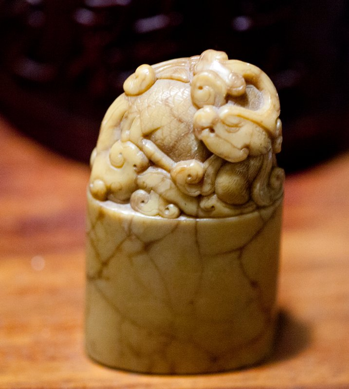 stamp with uncarved base/bottom; dragon carved on top; tan colored jade with brown veins. Former Classification: Jade