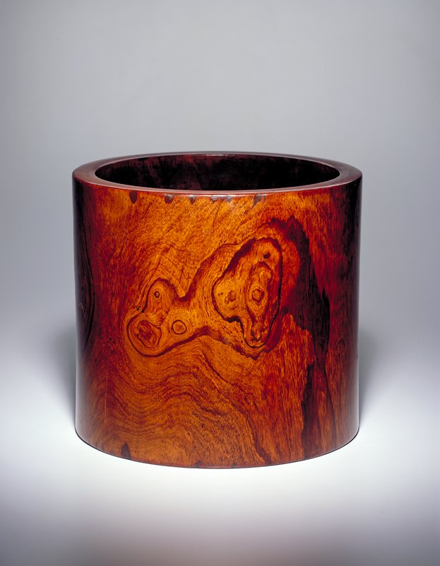 dark brown wood cylindrical container; natural design in wood resembles an animal form